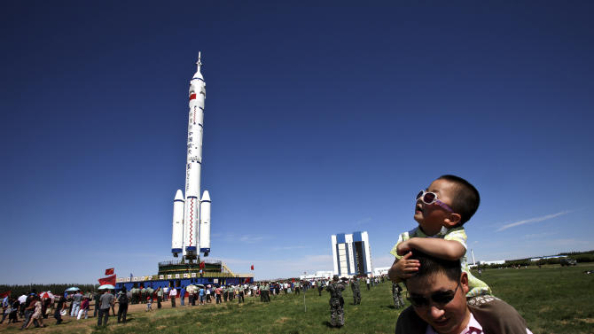A Chinese man carries his son walks near the Long March-2F rocket carrying the Shenzhou-9 spacecraft which moves to the launch pad at the Jiuquan launch center in Jiuquan, China's northwest Gansu province, Saturday, June 9, 2012. China will launch three astronauts this month to dock with an orbiting experimental module, and the crew might include its first female space traveler, a government news agency said Saturday. (AP Photo) CHINA OUT