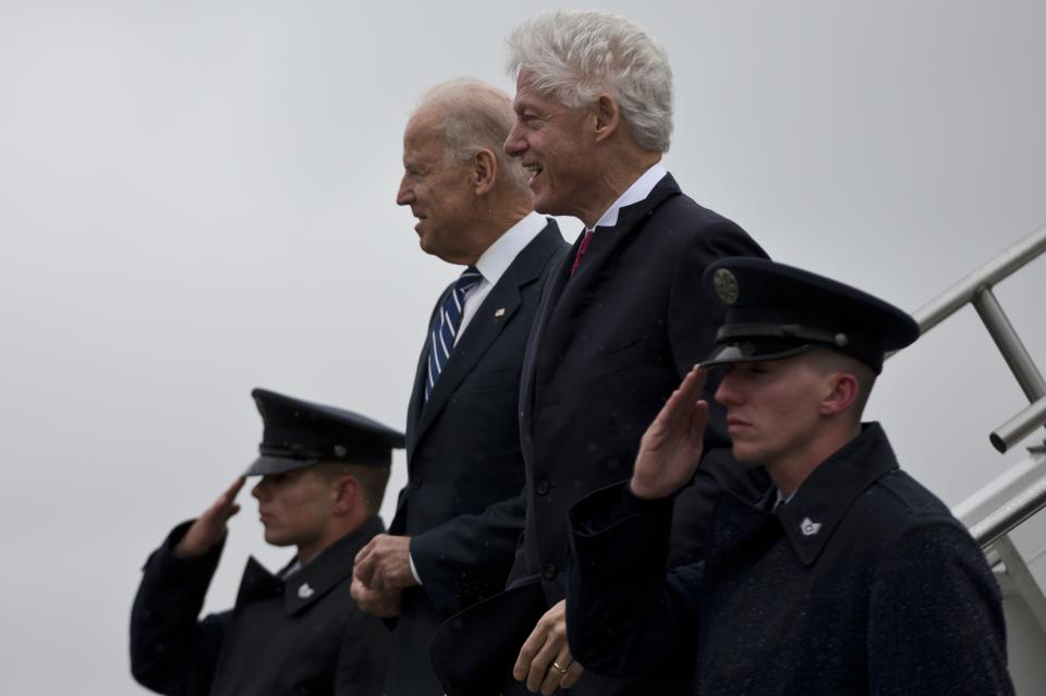 Vice President Joe Biden and former President Bill Clinton walk off of Air Force Two during a rainstorm, Monday, Oct. 29, 2012, in Youngstown, Ohio. (AP Photo/Matt Rourke)