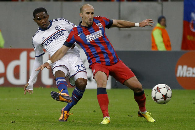 Chelsea's Samuel Eto'o, left, takes a shot at goal next to Steaua's Iasmin Latovlevici, rift, during the soccer Champions League group E match between Steaua Bucharest and Chelsea in Bucharest, Romani
