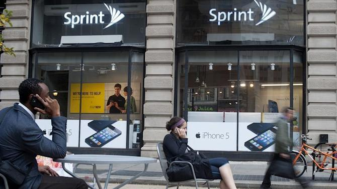 People talk on their cell phones as passers-by walk past a Sprint store in New York