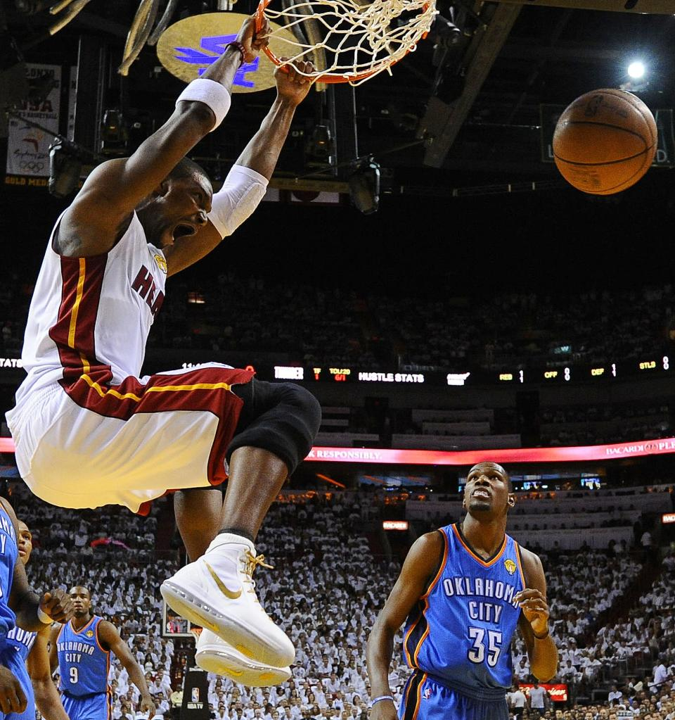 Miami Heat power forward Chris Bosh (1) dunks as Oklahoma City Thunder small forward Kevin Durant (35) looks on during the first half of Game 3 of the NBA Finals basketball series, Sunday, June 17, 2012, in Miami. (AP Photo/Larry W. Smith, Pool)