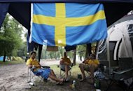 "Swedish fans sit next to their tents at the campsite ""Camp Sweden"" in Kiev. Local municipal councillor Olexandre Davidenko was quoted in Ukrainska Pravda as saying: ""I think the Swedes will come to regret their decision to camp there."""