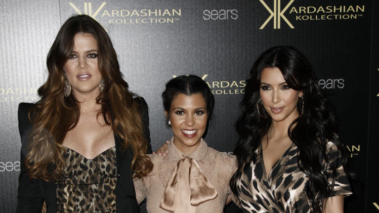 Khloe Kardashian, left, Kourtney Kardashian, center, and Kim Kardashian arrive at the Kardashian Kollection launch party in Los Angeles, Wednesday, Aug. 17, 2011. The Kardashian Kollection designed by the Kardashian sisters is available at Sears. (AP Photo/Matt Sayles)