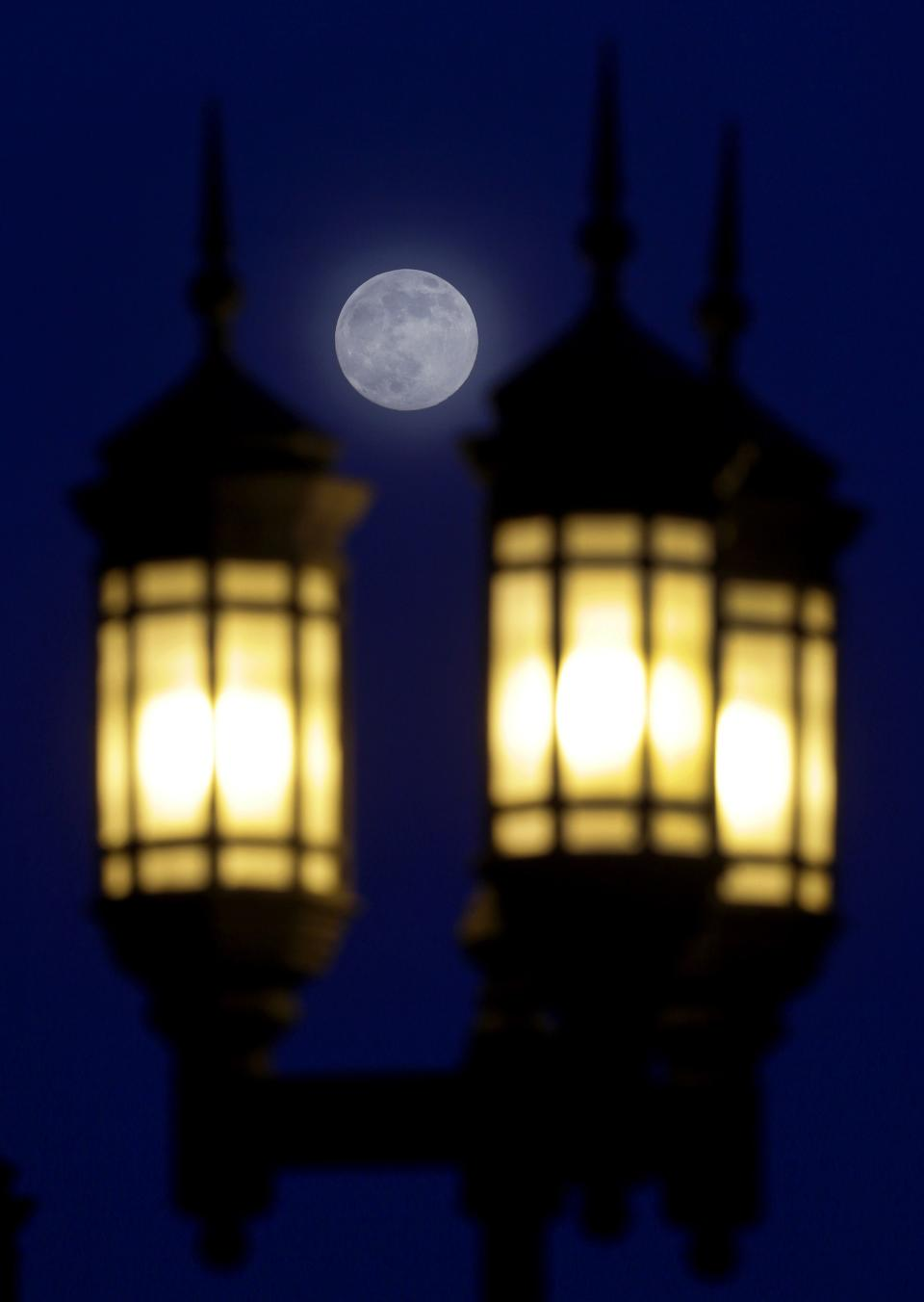 A full moon rises through a hazy sky over street lamps, Saturday, June 22, 2013, in Baltimore. The moon, which will reach its full stage on Sunday, is expected to be 13.5 percent closer to earth during a phenomenon known as supermoon. (AP Photo/Patrick Semansky)