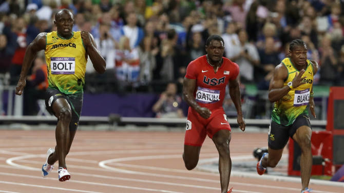 Jamaica's Usain Bolt, left, prepares to pass United States' Justin Gatlin, center,  and Jamaica's Yohan Blake, to win in the men's 100-meter final during the athletics in the Olympic Stadium at the 2012 Summer Olympics, London, Sunday, Aug. 5, 2012.(AP Photo/Kirsty Wigglesworth)