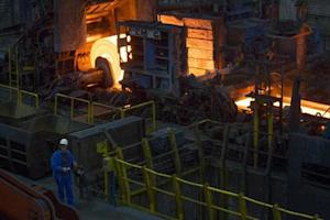 A worker stands in front of a rolling mill in the ArcelorMittal steel factory in Eisenhuettenstadt