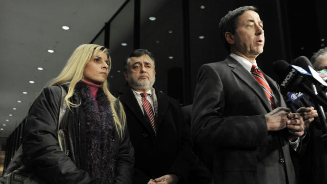 Bartender Karolina Obrycka, left, listens while her attorney Terry Ekl, right, speaks during a news conference in Chicago on Tuesday, Nov. 13, 2012.  Jurors awarded $850,000 in damages to Obrycka, who was beaten in February 2007 by off-duty Chicago police officer Anthony Abbate, who was admittedly drunk at the time.  Surveillance video of the hulking Abbate pushing Obrycka to the ground behind the bar at Jesse's Shortstop Inn, then repeatedly punching and kicking her went viral online. (AP Photo/Paul Beaty)