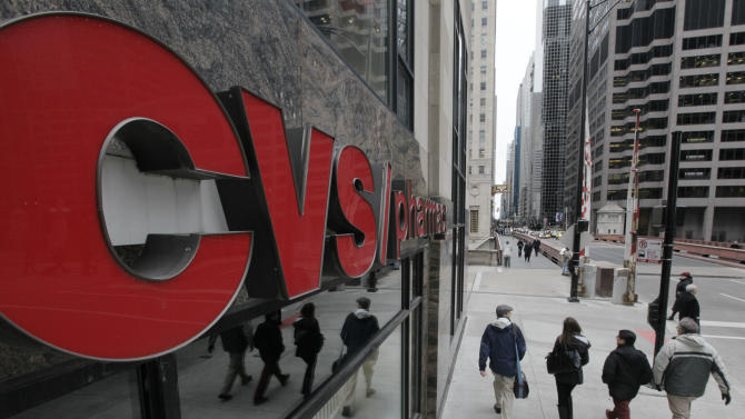 FILE - In this Feb. 7, 2012 file photo, pedestrians walk past a CVS store in Chicago. CVS Caremark Corp. is reporting their earnings on Tuesday, Nov.5, 2013. (AP Photo/M. Spencer Green, File)