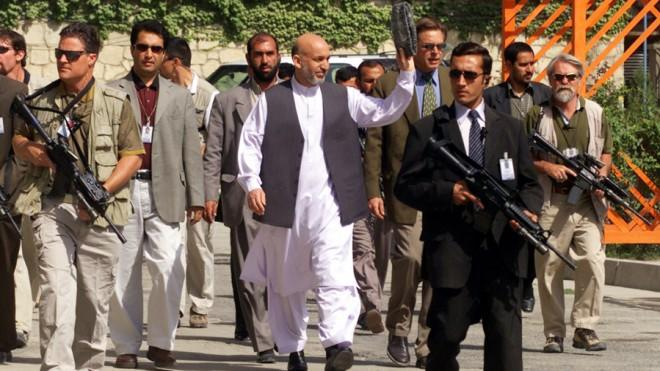Afghanistan President Hamid Karzai waves to presidential palace workers while walking to his office in 2003.