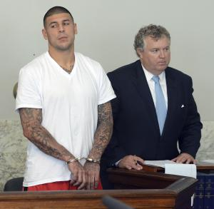 "FILE - In this June 26, 2013 file photo, former New England Patriots tight end Aaron Hernandez, left, stands with his attorney Michael Fee, right, during arraignment in Attleboro District Court in Attleboro, Mass. A police search of a secret ""flop house"" rented by Hernandez turned up boxes of ammunition and clothing police believe could be evidence in the murder case against him, according to court documents. (AP Photo/The Sun Chronicle, Mike George, Pool, File)"