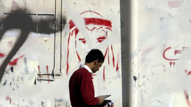 A man passes a wall painting depicting Redha Buhmeid, one of the protestors who allegedly died in past unrest and graffiti sprayed by anti-government protestors and painted over by police several times Sunday Nov. 13, 2011, in Malkiya village, Bahrain. Protests continue across Bahrain. (AP Photo/Hasan Jamali)