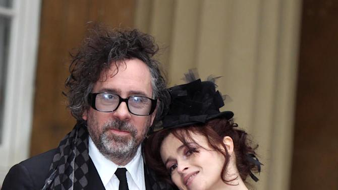 Helena Bonham Carter, right, and her husband Tim Burton pose with her Commander of the British Empire (CBE) medal, at Buckingham Palace, London, Wednesday, Feb. 22, 2012. (AP Photo/Sean Dempsey/PA) UNITED KINGDOM OUT  NO SALES  NO ARCHIVE