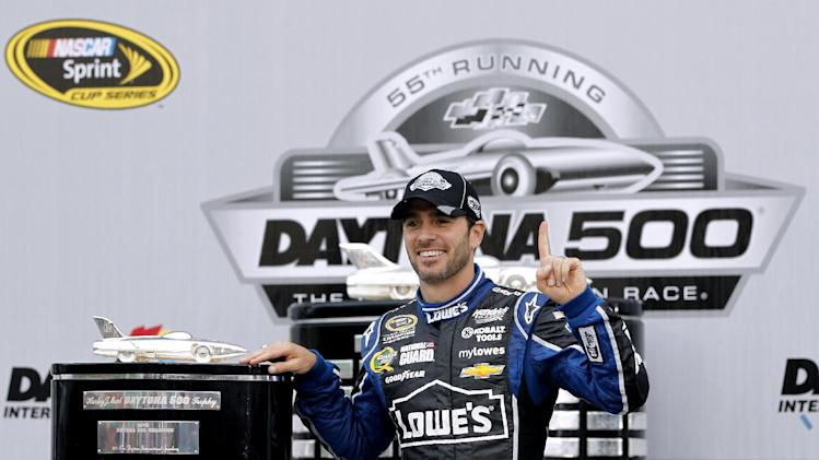 Jimmie Johnson poses for photos after winning the Daytona 500 NASCAR Sprint Cup Series auto race, Sunday, Feb. 24, 2013, at Daytona International Speedway in Daytona Beach, Fla. (AP Photo/Terry Renna)