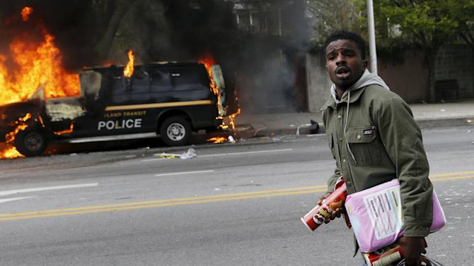 A man with looted goods walks by burned vehicles in Baltimore