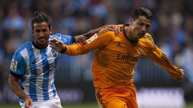 Real Madrid's Cristiano Ronaldo, right, duels for the ball against CF Malaga's Marcos Alberto Angeleri, left, during a Spanish La Liga soccer match at La Rosaleda stadium in Malaga, Spain, Saturday March 15, 2014