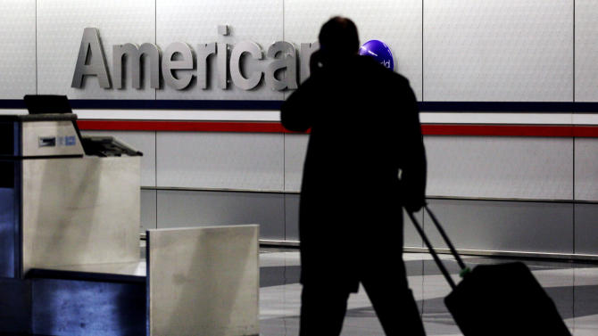 FILE - In this Tuesday, Nov. 29, 2011, file photo, a passenger walks through an American Airlines baggage claim area at O'Hare International Airport in Chicago. American and US Airways on Tuesday, April 8, 2014 announced changes to their policies on checked-bag fees and redeeming miles for free flights. Passengers traveling on American on miles they earned or who paid full price for an economy seat won't get to check two bags for free anymore. (AP Photo/Nam Y. Huh, File)