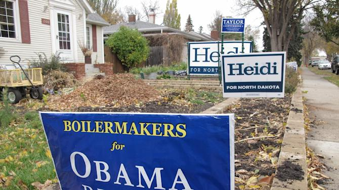 The front yard of a home in central Bismarck, N.D., displays yard signs supporting the re-election of Democratic President Barack Obama and Vice President Joe Biden, as well as the races of North Dakota Democratic U.S. Senate candidate Heidi Heitkamp and Ryan Taylor, the North Dakota Democratic candidate for governor, on Wednesday, Oct. 17, 2012. A lawsuit filed in federal district court in Bismarck, N.D., this week attempts to invalidate a state law that would require that the signs be taken down before midnight on the eve of Election Day, Nov. 6, 2012. The law bans campaigning on Election Day, and the lawsuit alleges the statute violates the free-speech rights of North Dakotans. (AP Photo/Dale Wetzel)