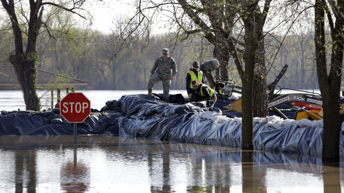 Members of the Missouri Nationals Guard and others work to shore up a temporary levee in an effort to hold back the swollen Mississippi River Saturday, April 20, 2013, in Clarksville, Mo. Communities along the Mississippi River and other rain-engorged waterways are waging feverish bids to hold back floodwaters that may soon approach record levels. (AP Photo/Jeff Roberson)