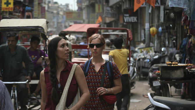In this Tuesday, April 2, 2013 photo, foreign tourists walk on a street near the railway station in New Delhi, India. Violence against women, and the huge publicity generated by recent attacks here, is threatening India's $17.7 billion tourism industry. A new study shows tourism has plunged, especially among women, since a 23-year-old Indian student was raped on a New Delhi bus and later died from her injuries, a case that garnered worldwide publicity. (AP Photo /Manish Swarup)