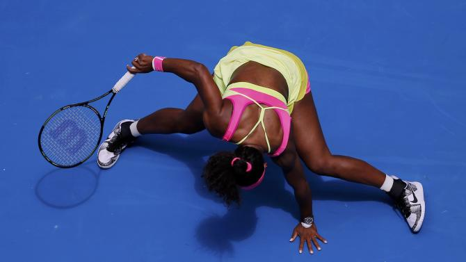 Williams of the U.S. leans over onto the court after reaching for a shot against Muguruza of Spain during their women's singles fourth round match at the Australian Open 2015 tennis tournament in Melbourne