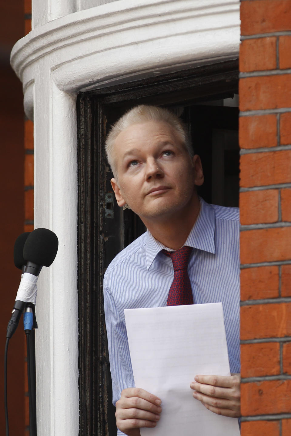 "WikiLeaks founder Julian Assange looks up as he retreats from the window of Ecuadorian Embassy in central London after making a statement to the media and supporters outside, Sunday, Aug. 19, 2012. Assange called on United States President Barack Obama to end a ""witch hunt"" against the secret-spilling WikiLeaks organization.(AP Photo/Sang Tan)"