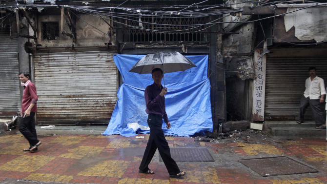 Commuters walk past closed shops at Zaveri Bazaar, one of the sites of Wednesday's serial explosions, in Mumbai, India, Friday, July 15, 2011. Investigators were examining forensic evidence and footage from closed circuit cameras Friday for clues about who orchestrated the triple bomb blasts that shook India's business hub of Mumbai and killed 17. (AP Photo/Rajanish Kakade)
