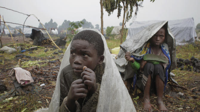 Internally displaced Congolese children shelter from the  rain under plastic sheets as they wait for aid to be distributed in Kibati, north of Goma,  eastern Congo, Wednesday  Aug. 8, 2012. Drenching rain punctuated by frightening bursts of thunder and forked lightning add to the misery of some of the 280,000 refugees from Congo's eastern rebellion, whose plight is highlighted by a visit from the U.N. humanitarian chief  Baroness Valerie Amos. (AP Photo/Jerome Delay)