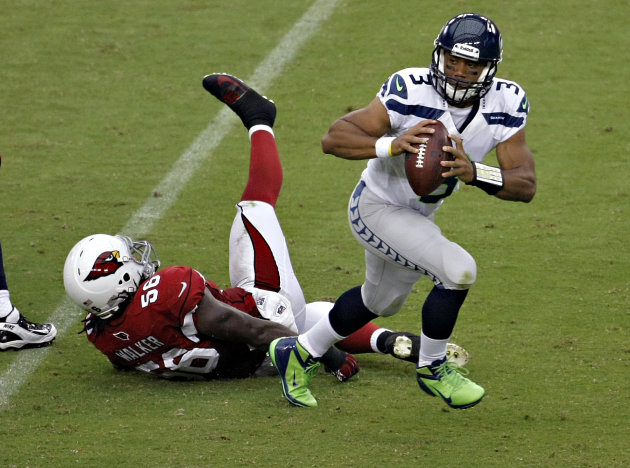 Seattle Seahawks quarterback Russell Wilson (3) escapes the reach of Arizona Cardinals linebacker Reggie Walker (56) during the first half of an NFL football game, Sunday, Sept. 9, 2012, in Glendale, Ariz. (AP Photo/Rick Scuteri)