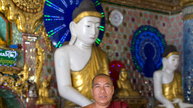 """In this picture taken on Thursday, Nov. 15, 2012, Buddhist monk Wizaya poses for a photograph at Shwedagon Pagoda in Yangon, Myanmar. """"I think America can work for the people. China only works for the government,"""" said Wizaya, a 47-year-old monk. Word of U.S. President Barack Obama's historic visit has spread quickly around Yangon, which is readying itself with legions of hunched workers painting fences and curbs, pulling weeds and scraping grime off old buildings in anticipation of the president's Monday arrival. (AP Photo/Gemunu Amarasinghe)"""