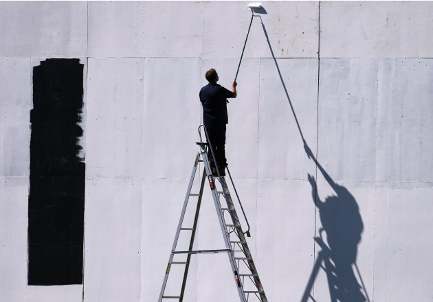 A groundsman paints the side-screen during an England cricket team training session in Wellington