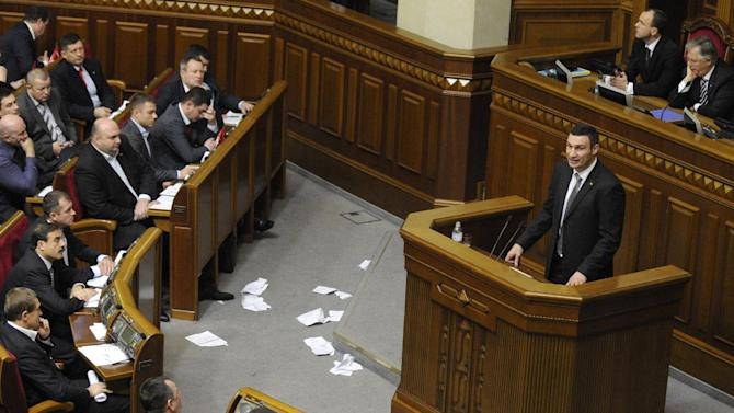 Chairman of the Ukrainian opposition party Udar (Punch) and WBC Heavyweight Champion boxer Vitali Klitschko, speaks to lawmakers during the first session of Ukraine's newly elected parliament in Kiev, Ukraine, Thursday, Dec. 13, 2012. Ukraine's newly elected parliament has chosen a pro-government speaker amid violent brawls between pro-presidential and opposition lawmakers. On Thursday, opposition lawmakers swarmed the parliament's presidium and a fight erupted with pro-government legislators. The opposition demanded that their opponents stop voting in place of their absent colleagues. (AP Photo/Sergei Chuzavkov)