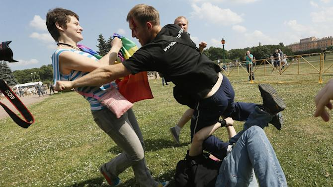 An anti-gay protester, center, attacks a gay rights activists during an authorized gay rights rally in St.Petersburg, Russia, Saturday, June 29, 2013. Police detained several gay activists, who were outnumbered by the protesters. Dozens of gay activists had to be protected by police as they gathered for the parade, which proceeded with official approval despite recently passed legislation targeting gays. (AP Photo/Dmitry Lovetsky)