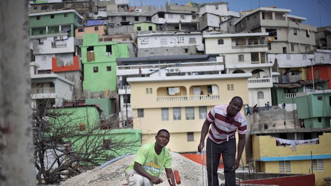 In this March 21, 2013 photo, workers paint red the exterior of a home in Jalousie, a cinder block shantytown in Petionville, Haiti. Jalousie is unique in that its mountainside presence makes it visible to people living in the wealthy district of Petionville. Critics have suggested that the choice of Jalousie for a makeover is as much about giving the posh hotels of Petionville a pretty view as helping the slum's residents. (AP Photo/Dieu Nalio Chery)