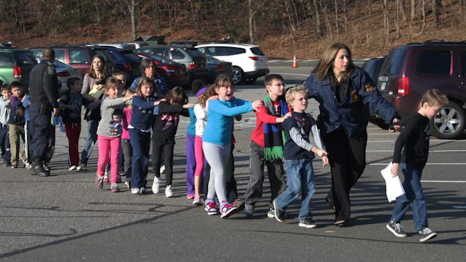 FILE - In this Friday, Dec. 14, 2012 file photo provided by the Newtown Bee, Connecticut State Police lead a line of children from the Sandy Hook Elementary School in Newtown, Conn. after a shooting at the school. Family members and others will gather in Newtown Friday June 14, 2013 with a moment of silence and calls to do more to control gun violence, as the town marks six months since the Sandy Hook school shootings. (AP Photo/Newtown Bee, Shannon Hicks, File) MANDATORY CREDIT: NEWTOWN BEE, SHANNON HICKS