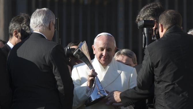 """Pope Francis looks at a replica of the Argentine soccer major league's trophy he was presented by a delegation of San Lorenzo soccer team, at the end of his weekly general audience in St. Peter's Square at the Vatican, Wednesday, Dec. 18, 2013. Pope Francis has celebrated his beloved San Lorenzo's victory in the Argentine soccer championship, hoisting up a replica of their trophy for all to see. A small group of team managers and players met with Francis on the steps of St. Peter's Basilica at the end of his Wednesday general audience. The group presented him with the replica of the trophy and a red and blue team jersey with """"Francisco Campeon"""" written on back. A clearly pleased Francis raised the trophy for all to see. San Lorenzo, of which then-Cardinal Jorge Mario Bergoglio was a registered fan, clinched the Argentine championship Sunday. (AP Photo/Alessandra Tarantino)"""
