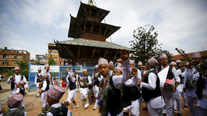 Devotees in traditional attire dance as they take part in a parade commemorating the Neku Jatra-Mataya festival, the Festival of Lights, in Lalitpur