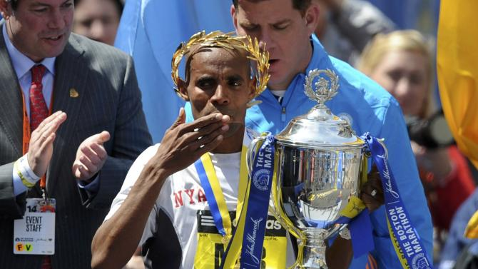 Meb Keflezighi of the U.S. celebrates with the trophy after winning the men's division at the 118th running of the Boston Marathon