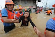 <p>Rescuers help a woman cross a flooded street as residents are evacuated from their homes in the village of Tumana, Marikina town, in suburban Manila on August 7, 2012. Army trucks hauled stranded residents from their homes, while enterprising children fashioned crude rafts out of scrap wood and banana tree trunks and charged people to ferry them around.</p>