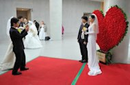 <p>A couple has their photograph taken during a mass wedding organised by the Unification Church, in Gapyeong, on February 17, 2013. Some 3,500 couples married in a mass wedding organised by the church - the first such event since the death of their 'messiah' and controversial founder Sun Myung Moon.</p>