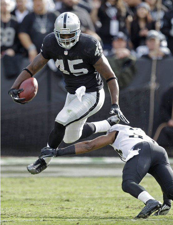 Oakland Raiders fullback Marcel Reece, top, carries the ball over New Orleans Saints cornerback Jabari Greer during the first quarter of an NFL football game in Oakland, Calif., Sunday, Nov. 18, 2012.