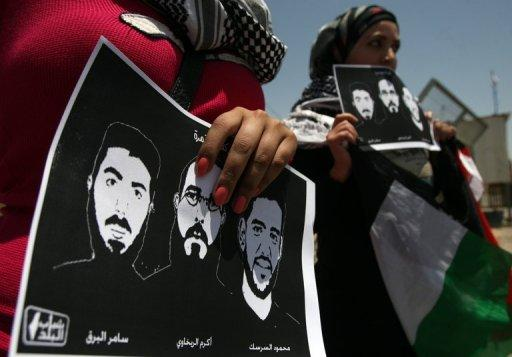 Palestinian protestors hold pictures of Mahmud Sarsak (right) and other prisoners during a demonstration near Ramallah