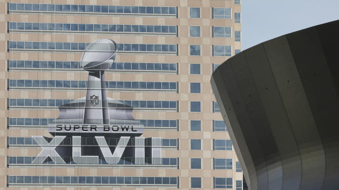 The NFL Super Bowl XLVII NFL football game logo is seen past the Mercedes-Benz Superdome on the face of an office building as preparations take place on Sunday, Jan. 27, 2013, in New Orleans. The Baltimore Ravens and San Francisco 49ers are scheduled to play in Super Bowl XLVII on Sunday, Feb. 3. (AP Photo/Patrick Semansky)