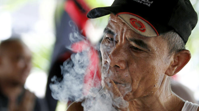 An Indonesian man smokes a cigarette in Jakarta, Indonesia, Tuesday, Sept. 11, 2012. Indonesian men rank as the world's top smokers, with two out of three of them lighting up in a country where cigarettes cost pennies and tobacco advertising is everywhere. (AP Photo/Achmad Ibrahim)