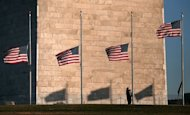 A National Park Service employee lowers flags at the base of the Washington Monument to half staff December 14, 2012 in Washington, DC. The residents of an idyllic Connecticut town were reeling in horror Saturday from the massacre of 20 small children and six adults at a school, in one of the worst mass shootings in US history