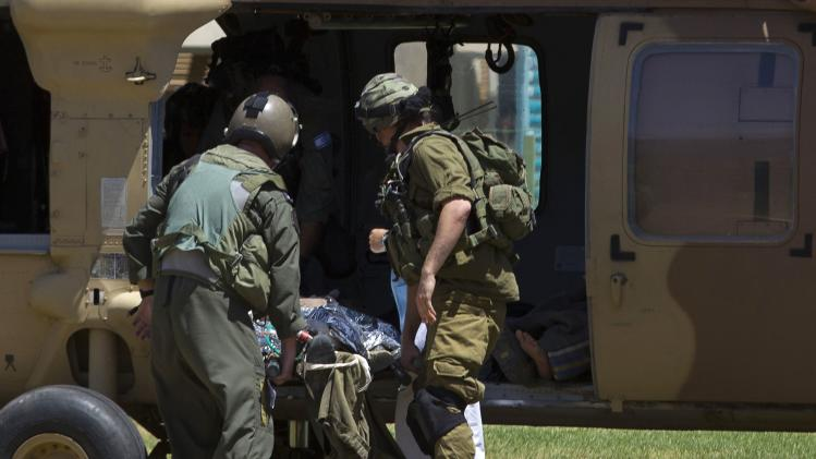 Israeli soldiers carry a wounded comrade out of helicopter in Beersheba