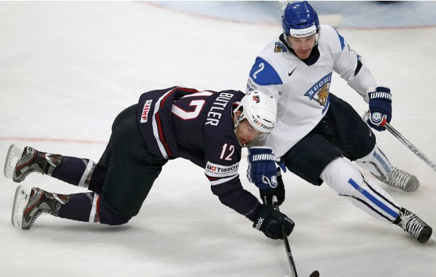 Team USA's Butler fights for the puck with Finland's Laakso during their 2013 IIHF Ice Hockey World Championship bronze medal match at the Globe Arena in Stockholm