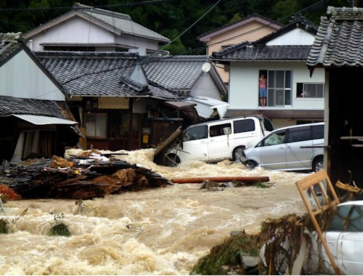 Overflowing water from a river floods a residential area in Nachikatsuura, central Japan, Sunday, Sept. 4, 2011. The center of the season's 12th typhoon was moving slowly north across the Sea of Japan, the Japan Meteorological Agency said. (AP Photo/Kyodo News) JAPAN OUT, MANDATORY CREDIT, NO LICENSING IN CHINA, FRANCE, HONG KONG, JAPAN AND SOUTH KOREA