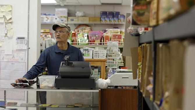 In this Thursday, Sept. 20, 2012 photo, Nai Sike, a former Buddhist monk who runs a grocery store with his wife, waits for a customer in his store in Fort Wayne, Ind. The city of 256,000, home to one of the nation's largest Burmese populations, has become an unlikely base for opposition to the former Burma's military regime. (AP Photo/Darron Cummings)