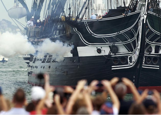 The USS Constitution fires one of her guns in Boston Harbor as a crowd looks on from the shore in Boston, Sunday, Aug. 19, 2012. The USS Constitution, the U.S. Navy's oldest commissioned war ship, sai