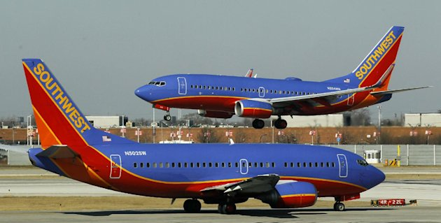"FILE - In this Feb. 9, 2012 file photo, a Southwest Airlines Boeing 737 waits to take off at Chicago's Midway Airport as another lands. Southwest Airlines' attempt to thank its online friends with a half-price ticket sale has backfired with customers inadvertently being billed multiple times, not feeling the ""luv."" Airline spokeswoman Ashley Dillon on Saturday, Aug. 4, 2012 blamed a ""technology glitch"" for the duplicate billings to debit and credit cards. (AP Photo/Charles Rex Arbogast, File)"